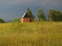 Small house in the middle of the field royalty free stock photo