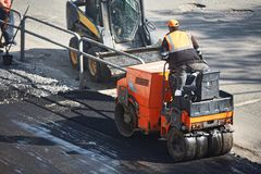 A small machine for laying a new asphalt. Asphalt paving. royalty free stock photography
