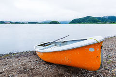 Small orange row boat parks at shore at lake Kawaguchiko, Japan Stock Photos