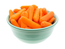 Small organic baby carrots in a green bowl Stock Photo
