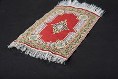 Small oriental carpet miniature on a black. royalty free stock photos