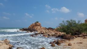 Small outcrop of rock in a sea shore. Small outcrop of rocks with the waves lashing against it, and a small tree on the sea shore Stock Image