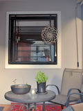 Small outdoor private patio with plants on the table. And dream catcher on the window stock photos