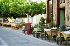 Small outdoor restaurants at the pedestrian area at center of Kalavryta town near the square and odontotos train station, Greece. Small outdoor restaurants and stock image