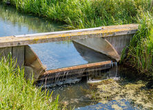 Small overflowing weir controls the water management in a ditch. Small overflowing weir controls the water management in a Dutch ditch on a sunny day in the Stock Photo