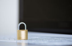 Small padlock sitting on white computer keyboard, online security concept Royalty Free Stock Image