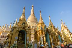 Small pagodas and Shwedagon Pagoda in Yangon. Small pagodas and statues in front of the gilded Shwedagon Pagoda in Yangon, Myanmar on a sunny day Royalty Free Stock Photography