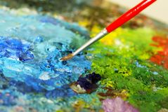 Small painbrush is mixing colors stock images