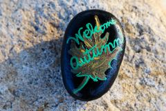 A small painted rock with a leaf that states Welcome Autumn Royalty Free Stock Photography