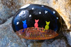 Small painted rock with picture of three colorful cats on a fence stock photography