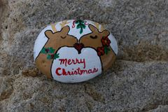 Small painted rock with two reindeer kissing stock image