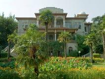 Small palace. Yard of small palace - palms, flowers Stock Photo