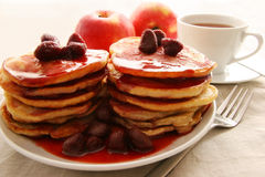 Small pan-cakes. Two piles of small pan-cakes with strawberries Royalty Free Stock Photo
