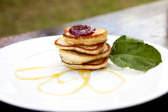 Small Pancakes Covered With Jam. Pancakes On A Plate Covered With Jam And Maple Syrup With Mint On The Side Stock Image