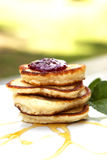 Small Pancakes Covered With Jam. Pancakes On A Plate Covered With Jam And Maple Syrup With Mint On The Side Royalty Free Stock Photos