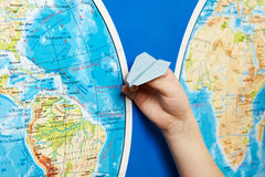 Small paper airplane on intercontinental flight to world map Stock Photography