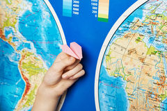 Small paper airplane on intercontinental flight to world map Royalty Free Stock Photography