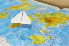 Small paper airplane over a geographical map of the world. selective focus. Concept: air travel, cargo delivery, travel, international messages, mail stock photos
