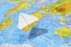 Small paper airplane over a geographical map of the world. selective focus. Concept: air travel, cargo delivery, travel, international messages, mail stock image