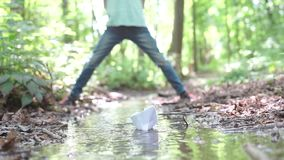 A small paper boat sailing along a stream. A small paper boat floating on a stream, against the background of children stock video footage