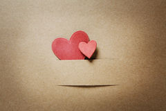 Small paper cut red hearts. On earthy colored paper Stock Photography