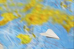 A small paper plane flies over a blurred abstract geographical map of the world. stock images