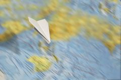 A small paper plane flies over a blurred abstract geographical map of the world. Concept of air travel, travel, mail, communication royalty free stock photography