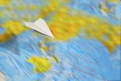 A small paper plane flies over a blurred abstract geographical map of the world. Concept of air travel, travel, mail, communication royalty free stock images