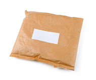 Small paper post parcel with blank label Stock Image
