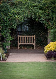 Small Park Bench in Ivy Alcove Royalty Free Stock Images