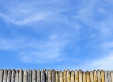Sharp stockade. A small part of the sharp stockade made of pine against the blue sky, the landscape in the spring stock image
