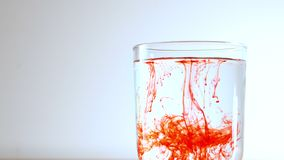 Small particles of red substance fall into a transparent glass with water, dissolve and leave a long trail