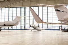 Small Passenger Airplane Leaving Bright Hangar. Small Passenger Airplane Leaving Brightly Lit Hangar Through Opening Glass Doors with View Past Tails of Aircraft Stock Image