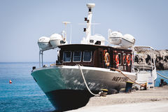 Small passenger boat parked near pier of Loutro town on Crete island. Stock Photography