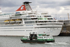 Small passenger ferry alongside cruise ship Stock Photos