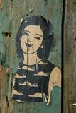 Small paste-up of a woman on a wooden post royalty free stock photos