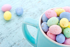 Small pastel easter eggs in a blue cup Stock Photo