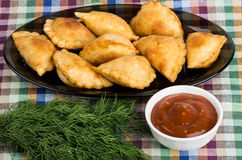 Small pasties, bowls with tomato sauce, dill Stock Image
