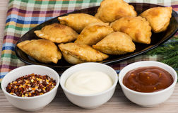 Small pasties, bowls with tomato sauce, mayonnaise, spices Stock Image