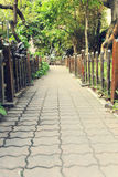 Small path in garden, brick pavement with wood fence Royalty Free Stock Photo