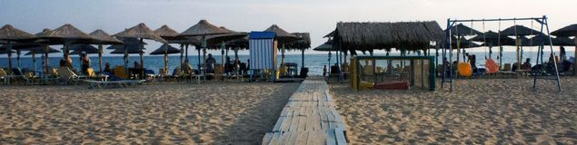 Small pathway in a summer beach. A picture of a summer beach with people . and a small wooden  pathway to the sea,in a small town in Greece,New Moudania,in a Royalty Free Stock Photography