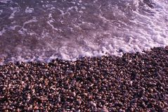 A small pebble is washed by sea waves Royalty Free Stock Photos