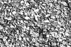Small pebbles / stone shingle wallpaper backdrop in black and white royalty free stock images
