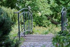 Small pedestrian bridge between trees. `Planten un Blomen ` city garden in Hamburg royalty free stock image