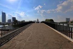 Small pedestrian concrete bridge over a narrow city river. This summer Royalty Free Stock Image