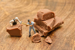 Small people crumble chocolate. The concept of cooking.  Royalty Free Stock Photos