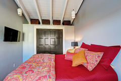 Small perfect bedroom with red bedding and grey walls. Royalty Free Stock Photo