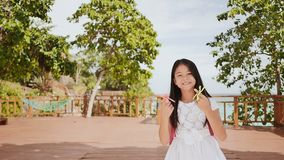 A small philippine schoolgirl shows spinning spinners. Tropical landscape. Summer. Childhood. A small philippine schoolgirl shows spinning spinners. Tropical stock video footage