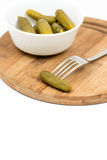 Small pickles in the white bowl and pickle on the fork.  Royalty Free Stock Image