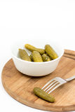 Small pickles in the white bowl and pickle on the fork.  Stock Images
